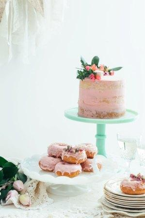 pink cake with donuts on a stand